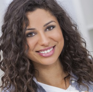 Headshot of Eva Guevara, brown hair curly - smiling
