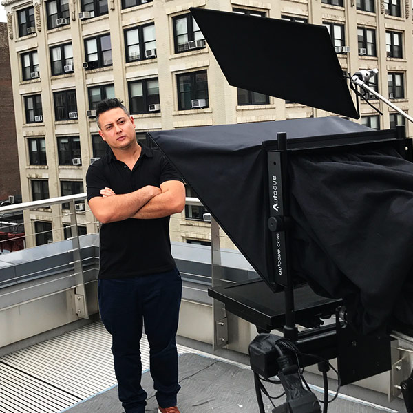 Michael Gonzalez standing next to Teleprompter setup on set
