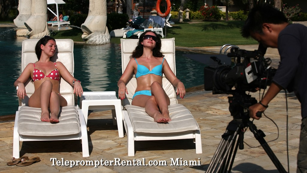 Teleprompter & Video Camera with two women in swimsuits on lounge chairs.