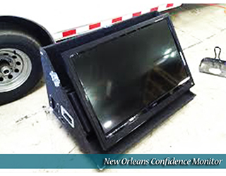 New Orleans Confidence Monitor unit on the curb (car wheel visible)