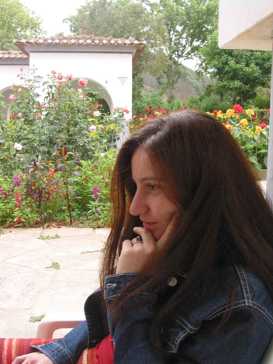 Benedita, long brown hair, pensive in beautiful garden