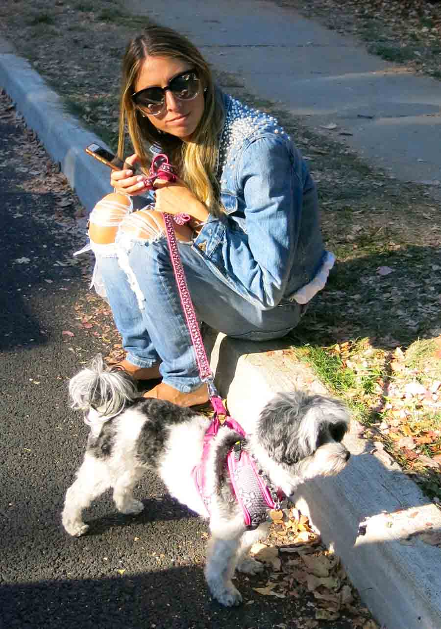 Denim clad young girl sitting on the curb with dog