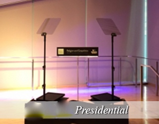 Two Presidential Prompter units on stage flanking a glass podium no people