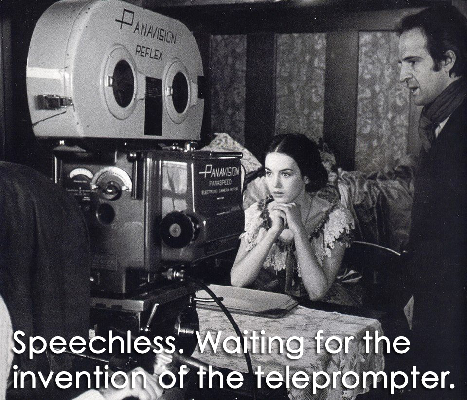 Two actors sitting and looking into the hige Panavision film cameras with out saying anything . with caption speechless waiting for the invention of the Teleprompter