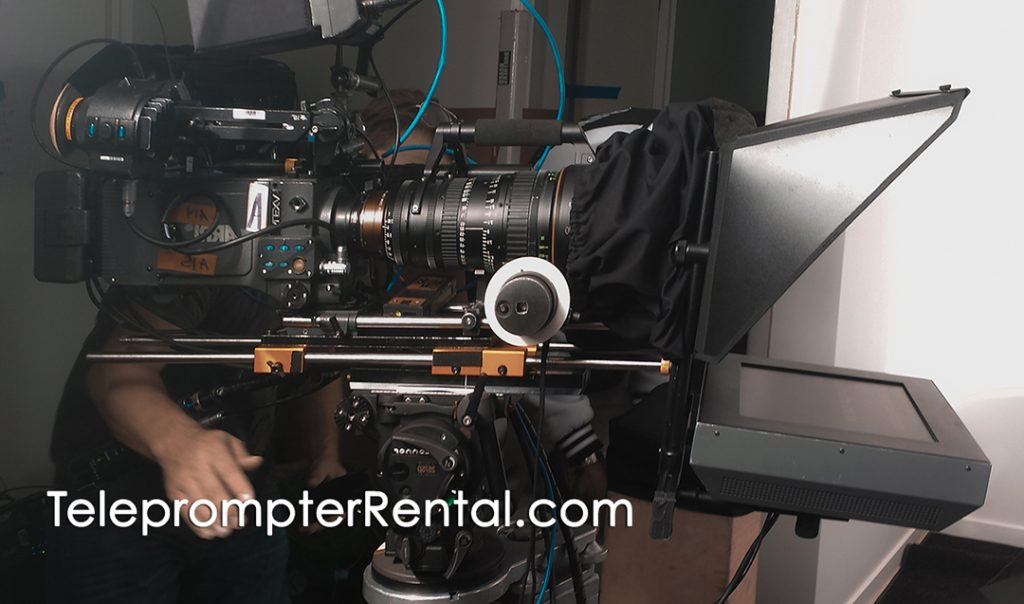 Huge camera an long lens on AutoCur Gold Plate teleprompter with caption TeleprompterRental.com